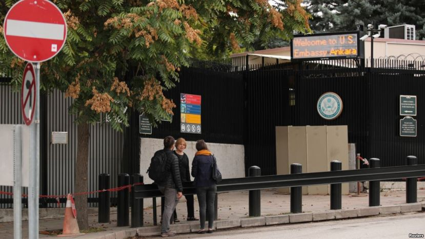 (1/2)FILE - People are seen in front of the visa application office entrance of the U.S. Embassy in Ankara, Turkey, Oct. 9, 2017. The U.S. suspended all non-immigrant visa services in Turkey Oct 8. and has since resumed only limited services.