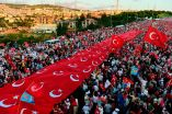 Turks standing under a collection of Turkish national flags on Saturday in Istanbul.
