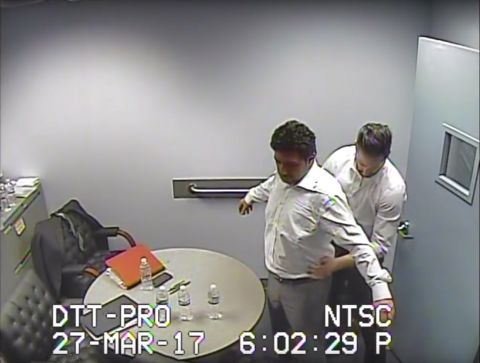 Taken from federal surveillance footage, this still image shows U.S. authorities frisking Mehmet Hakan Atilla after his arrest on March 27, 2017. A former manager at the Turkish state-run bank Halkbank, Atilla is being tried in New York over transactions that flouted sanctions against Iran.